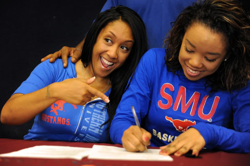 """Twelfth grader Mikayla Reese, 17, signs a letter of intent for a basketball scholarship Nov. 13 at Sand Creek HIgh School in Falcon School District 49. Reese is set to play for Southern Methodist University in Dallas. During a ceremony with two other seniors accepting a scholarship to play basketball, Reese was highlighted as a """"very intelligent player"""" who's great in transition and leading her team."""